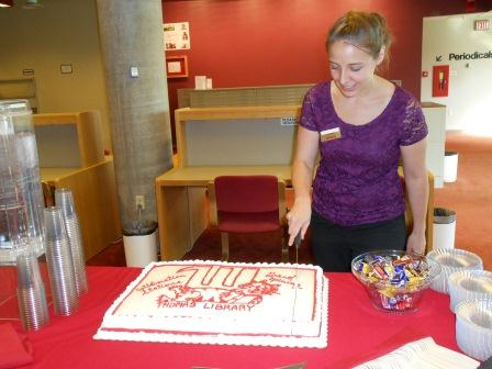 Kristen Gibson cuts the cake at the Collaboration Station grand opening.